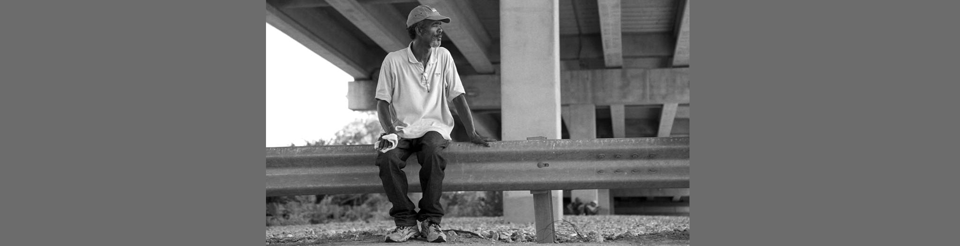 Man sitting under bridge